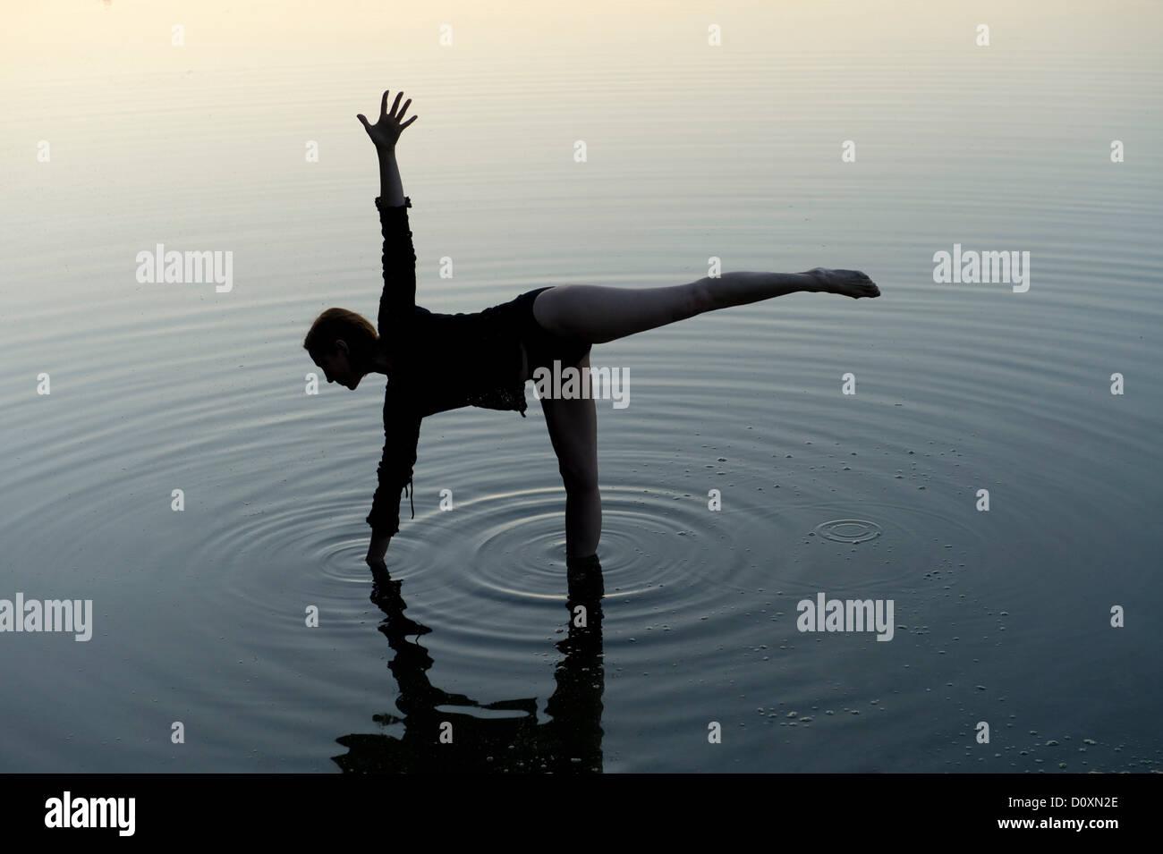 Woman in yoga pose in lake - Stock Image