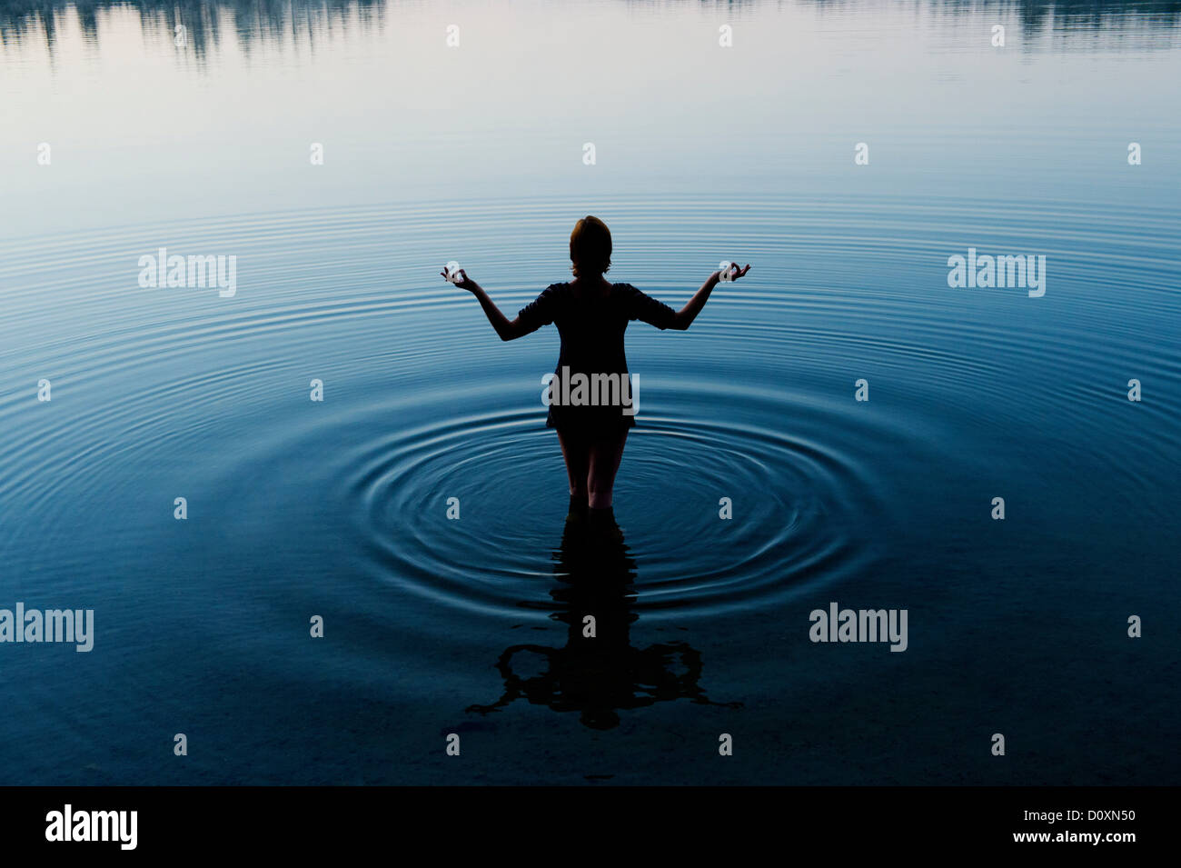 Woman meditating in peaceful lake - Stock Image
