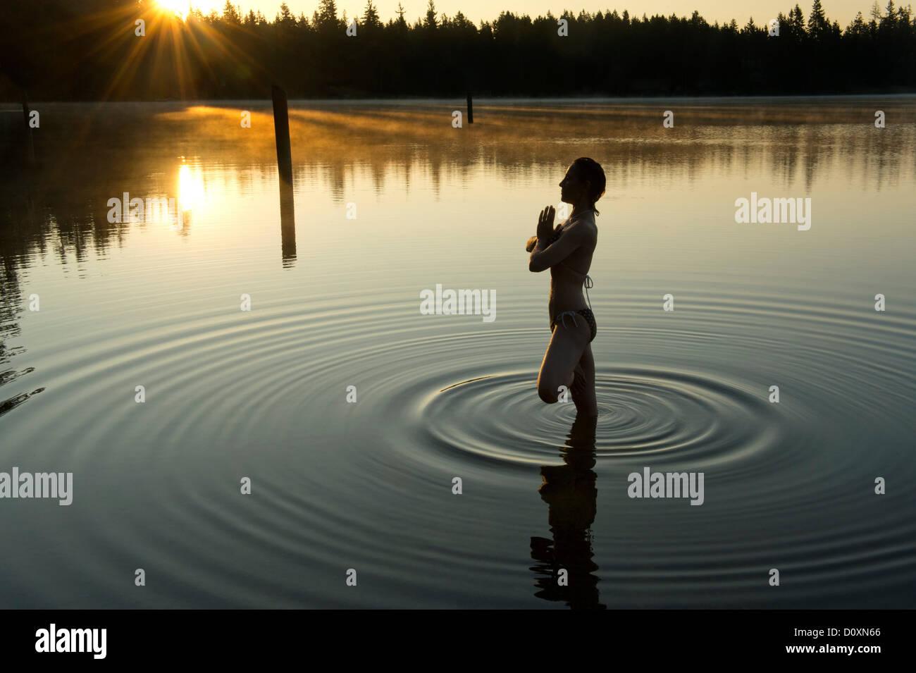 Woman meditating in calm lake - Stock Image