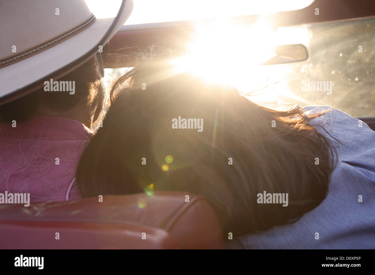 Woman resting head on boyfriend's shoulder as he drives in sunlight - Stock Image