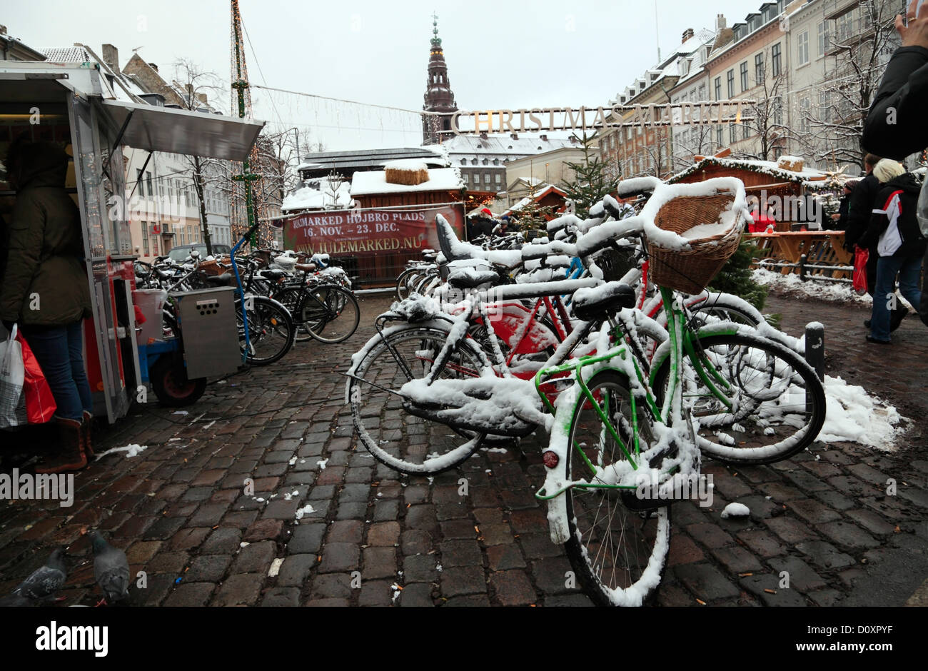 Snow covered bicycles at the Christmas market in Højbro Plads (Hoejbro Square) on Strøget (Stroeget) in - Stock Image