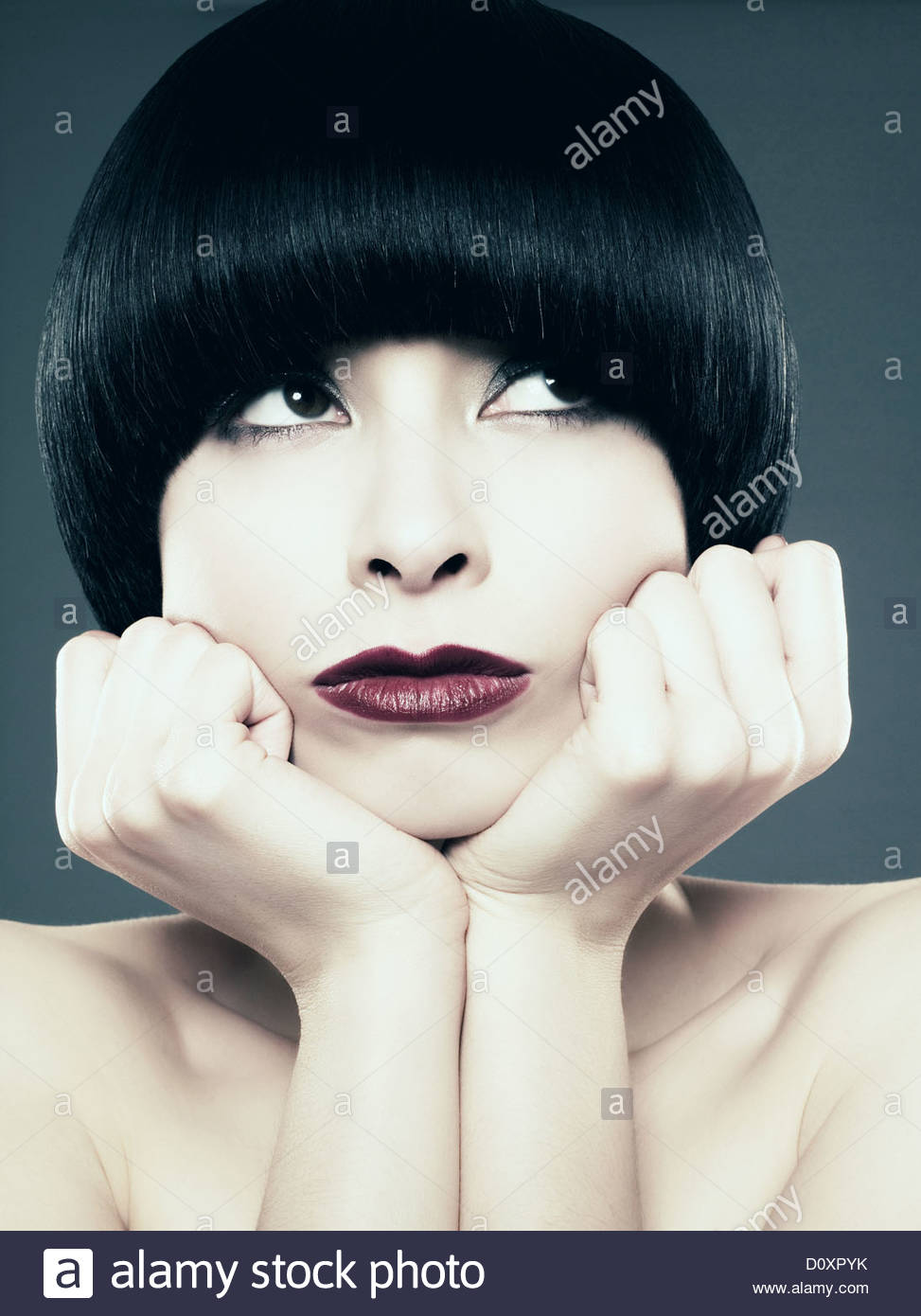 Young woman with black bob land hands on chin - Stock Image