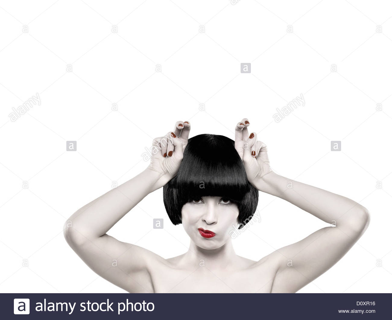 Young woman with black bob making bunny ears - Stock Image