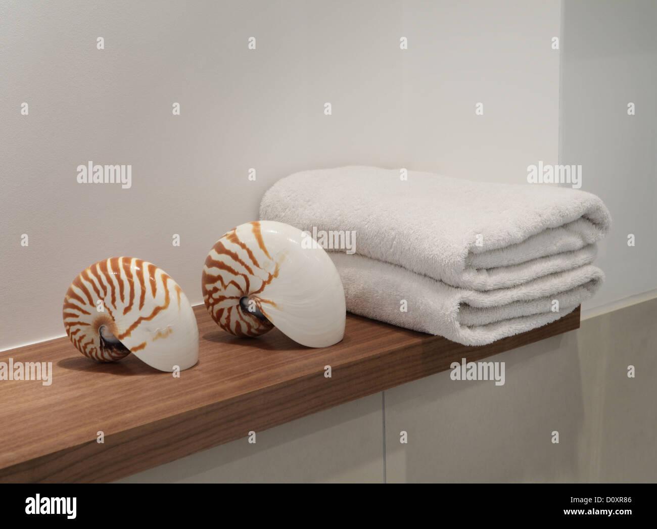 Seashells and towels on shelf - Stock Image
