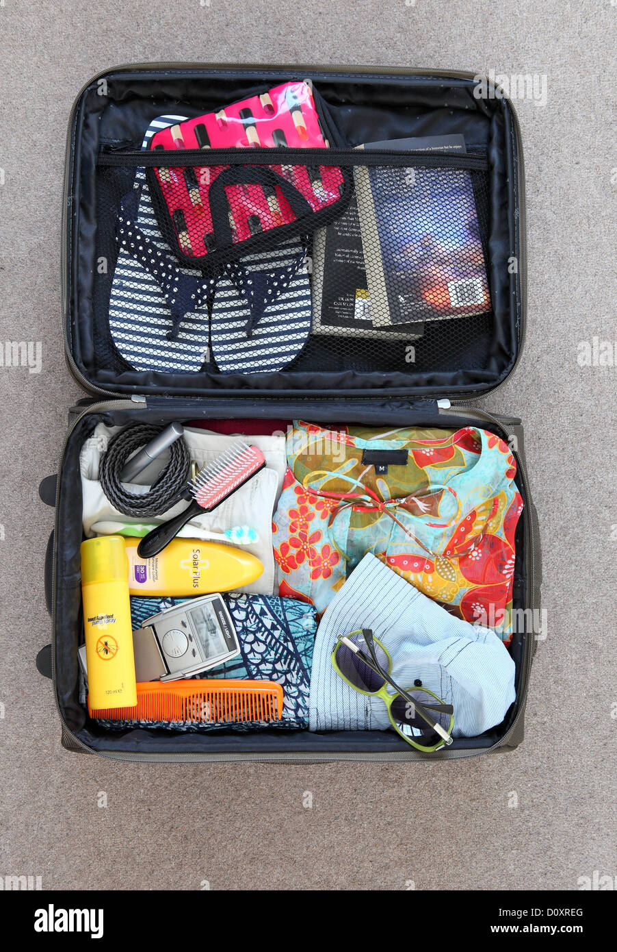 Suitcase packed for vacation - Stock Image