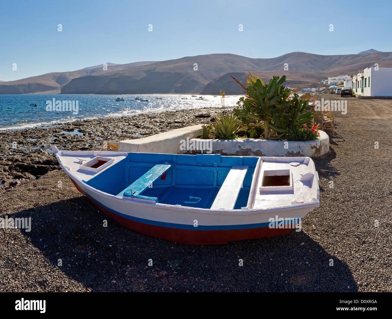 Spain, Lanzarote, Playa Quemada, Fishing dinghy, city, village, water, summer, mountains, sea, Canary Islands, - Stock Image
