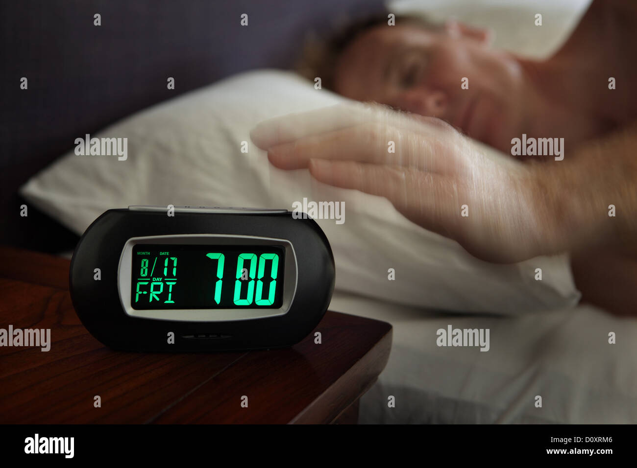 Man reaching for alarm clock Stock Photo