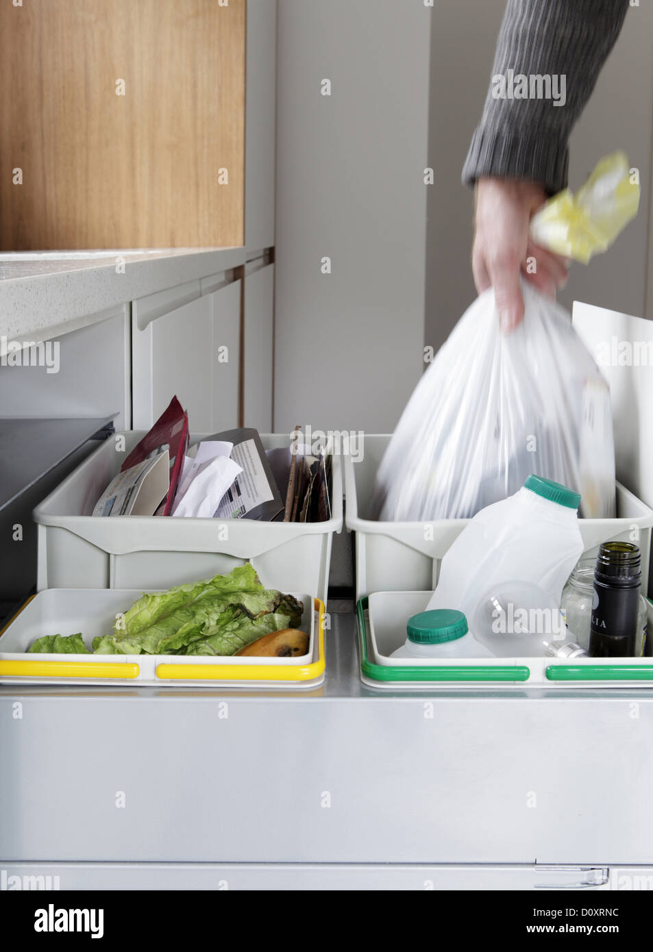 Person removing rubbish bag from waste and recycling drawer - Stock Image