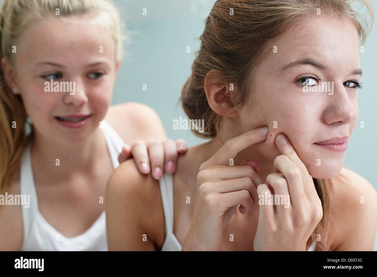 Girl squeezing a spot, friend with hand on shoulder - Stock Image