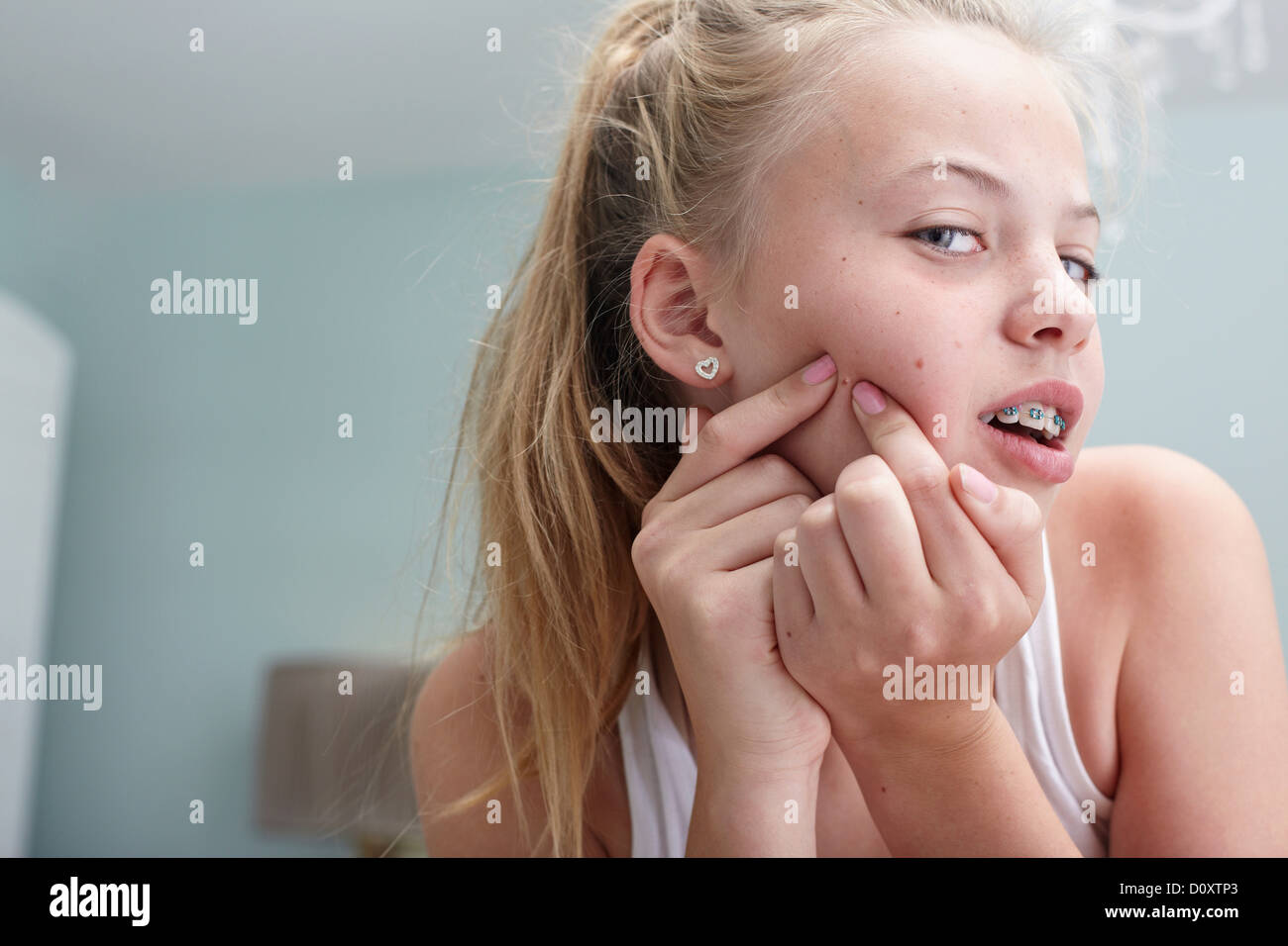Teenage girl squeezing a spot - Stock Image