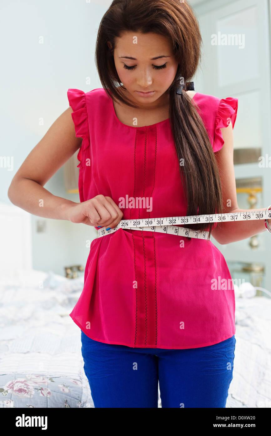 Teenage girl measuring her waist - Stock Image