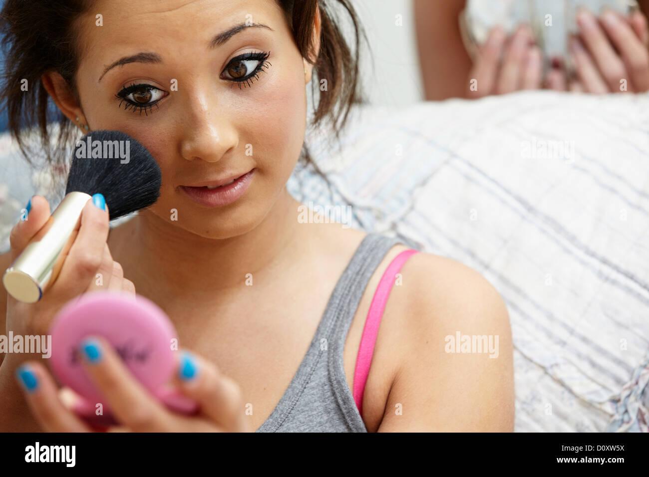 Teenage girl applying makeup - Stock Image