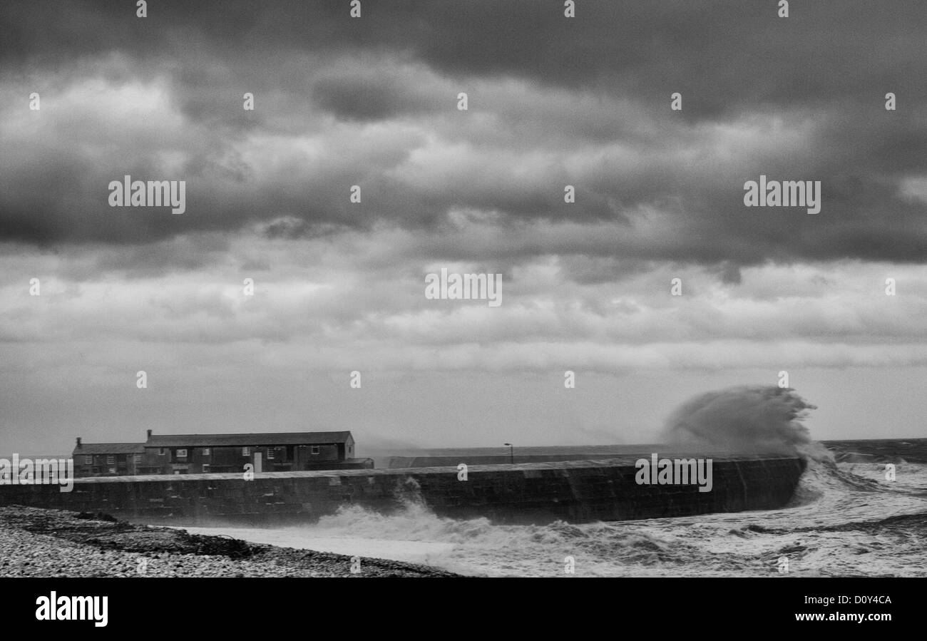 Heavy waves breaking over the wall of The Cobb, Lyme Regis during storm - Stock Image