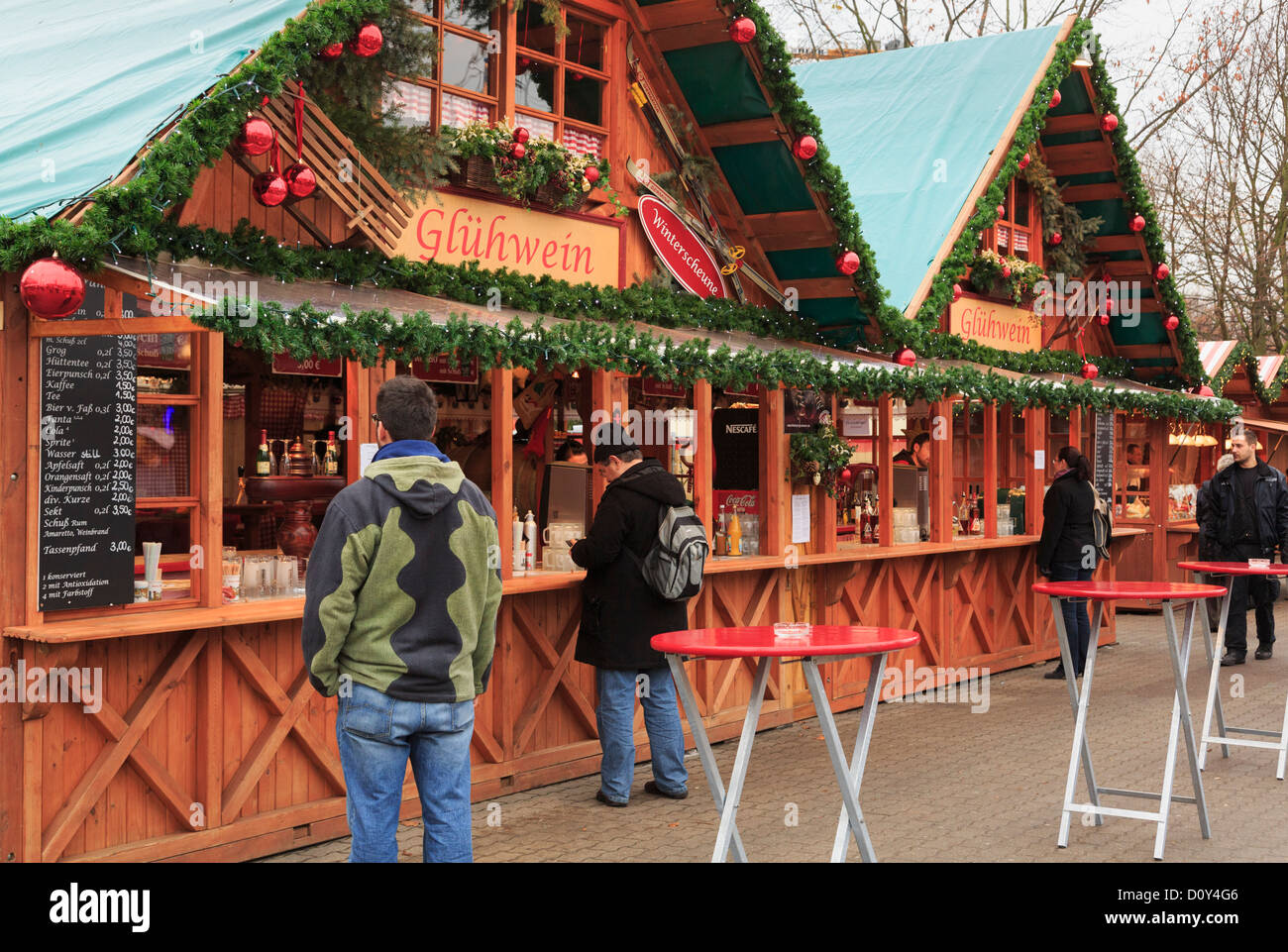Customers buying at a Christmas market stall selling drinks and traditional warm Gluhwein at Alexanderplatz, Berlin - Stock Image