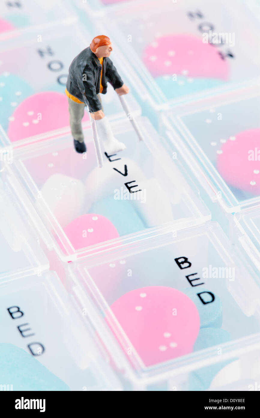 Mini Figure with Broken Leg on Pill Box - Stock Image