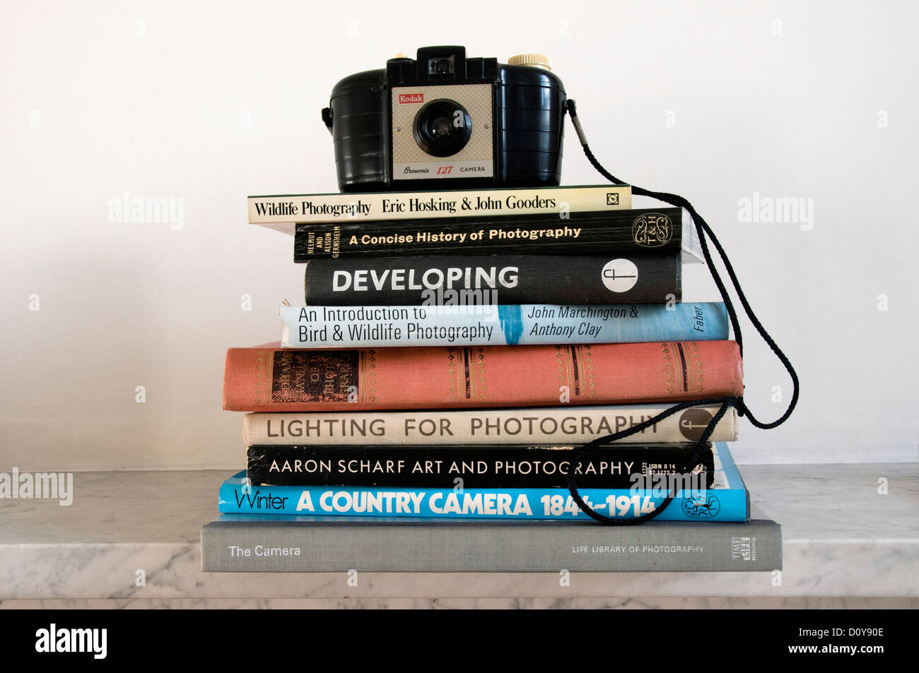 Pile of vintage photographic books with Kodak Brownie 127 camera on top - Stock Image