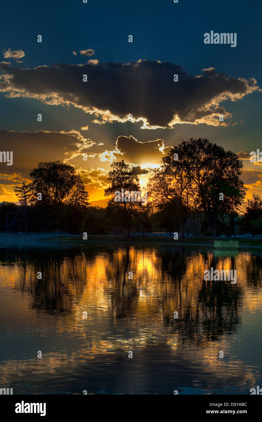 Clouds and Inspirational Sunset with Trees and Lake. - Stock Image