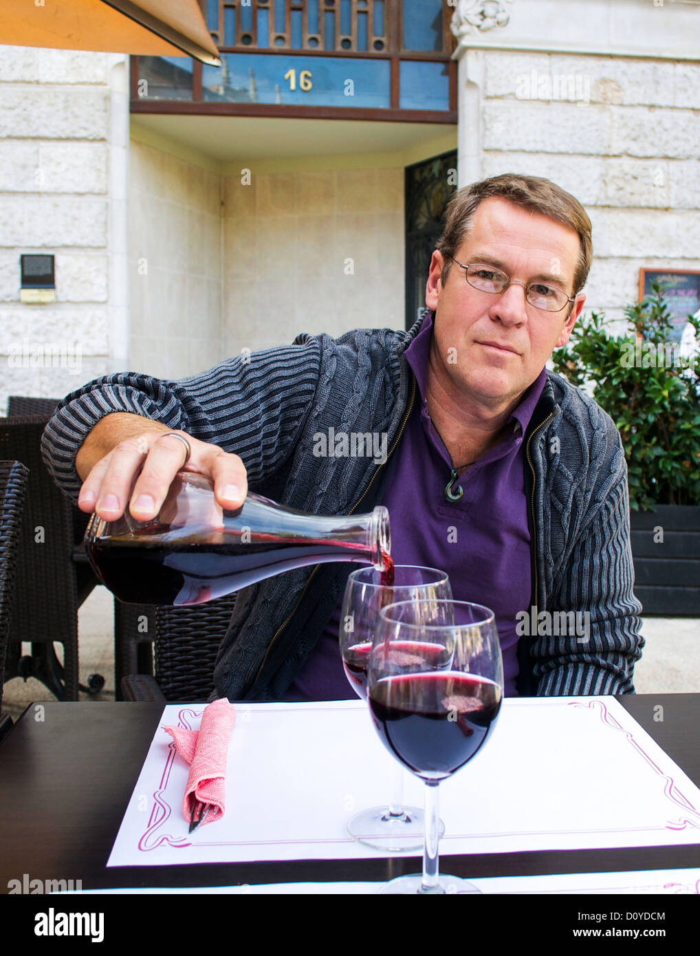 Man pouring a glass of red wine at a sidewalk cafe in Spain. - Stock Image