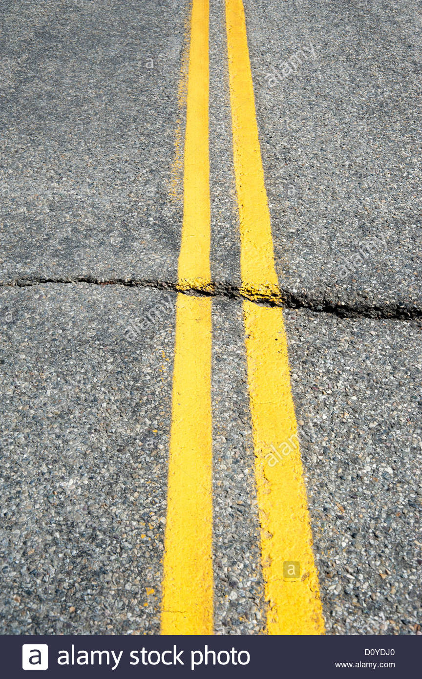 Double yellow line on road with crack through pavement - Stock Image