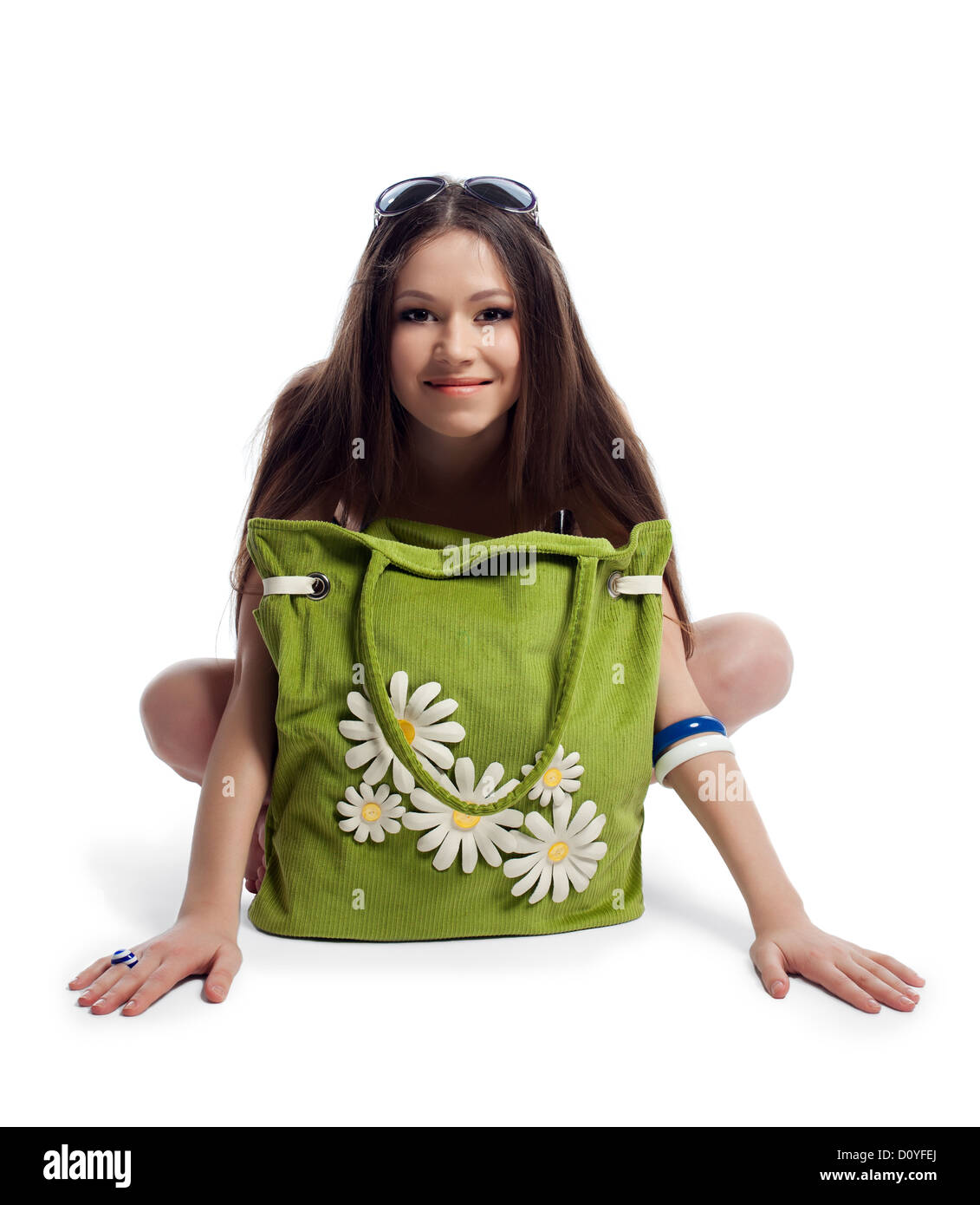 Yong woman sit with green beach bag smile isolated - Stock Image