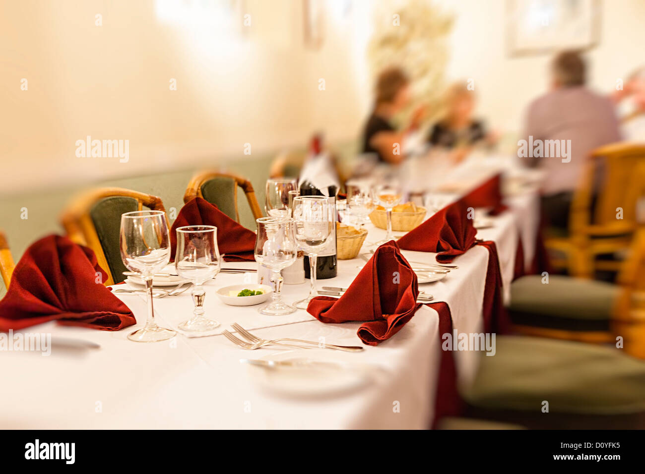 People in restaurant with focus on table with places laid ready, UK - Stock Image