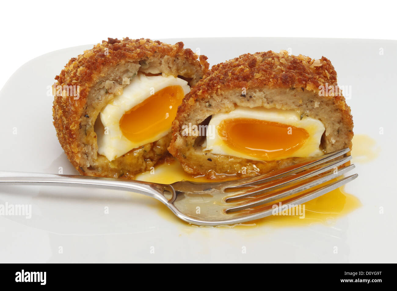 Runny Scotch egg on a plate with a fork - Stock Image