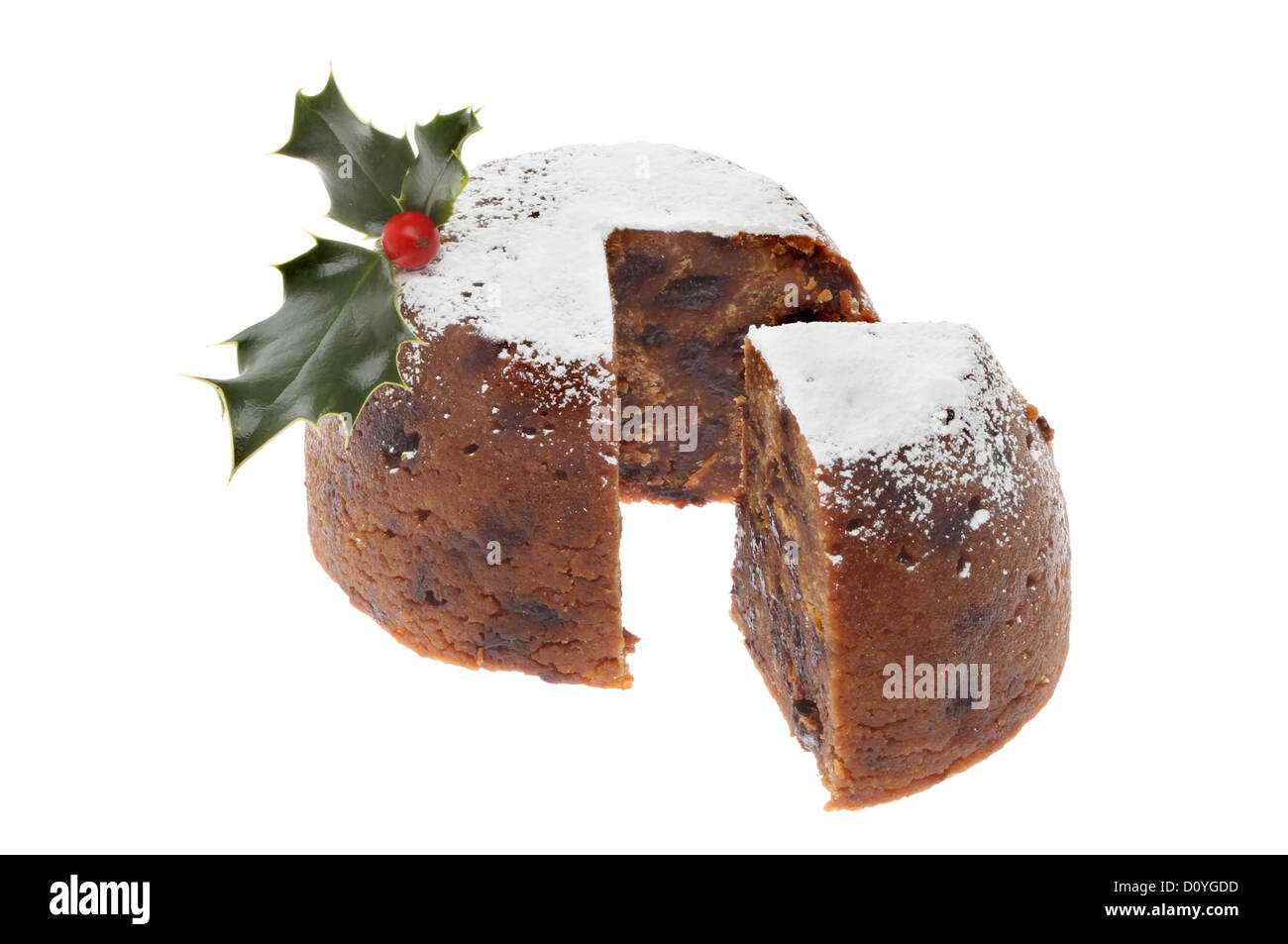 Christmas pudding dusted with icing sugar and decorated with holly with a slice cut out isolated against white - Stock Image