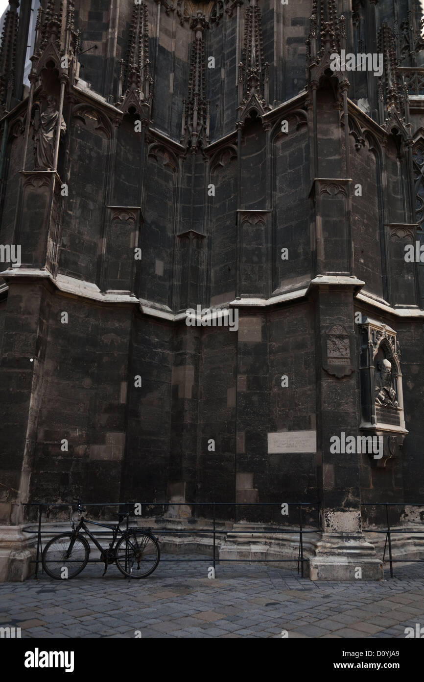 A bicycle parked outside Vienna's Gothic Stephansdom, centuries of soot and pollution have turned it's limestone - Stock Image