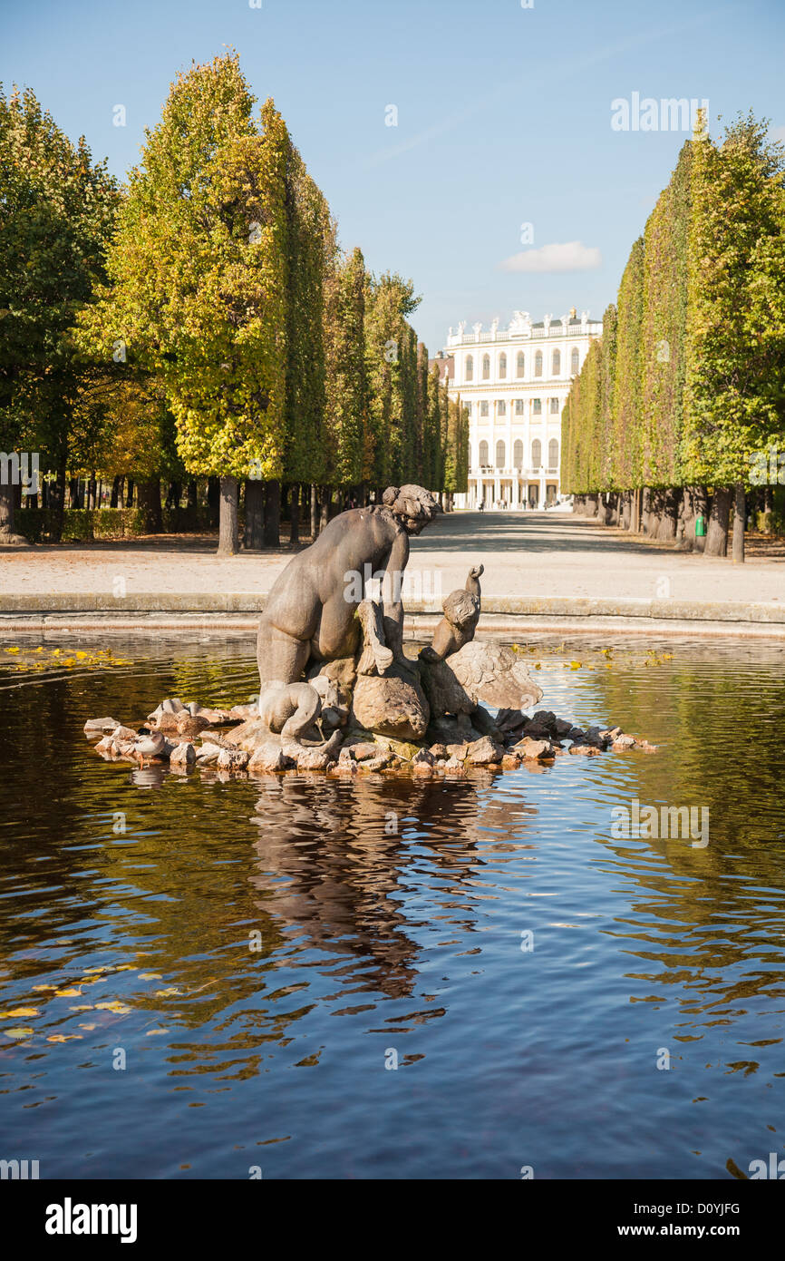 Sculpture in the center of a pond in the Schönbrunn Gardens, with a wall of tall straight hedges leading up - Stock Image