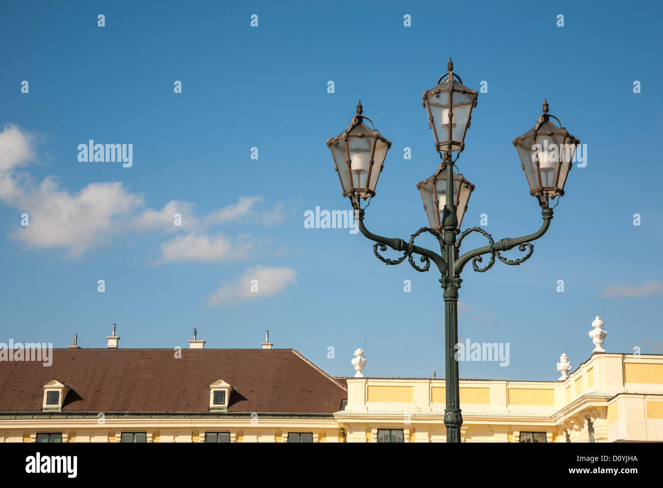 Ornate old iron street lamp inside the grounds of Vienna's yellow Schönbrunn Palace against a blue sky - Stock Image