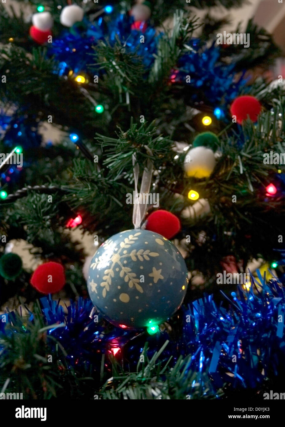 Snowflake-themed bauble on a Christmas tree decorated elsewhere with tinsel. - Stock Image
