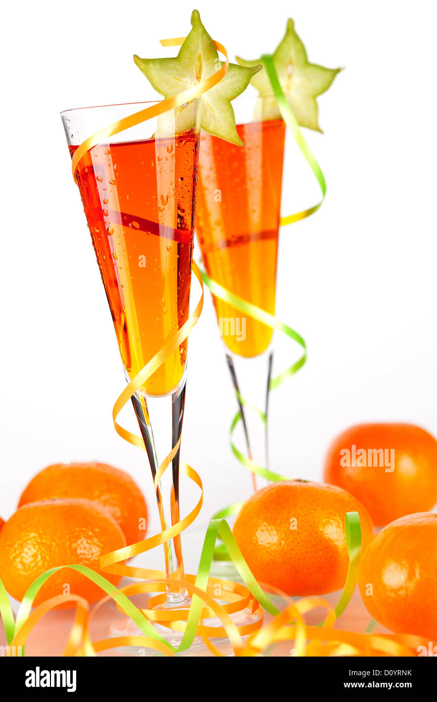 Two orange alcohol cocktails with carambola and mandarines isolated on white background - Stock Image