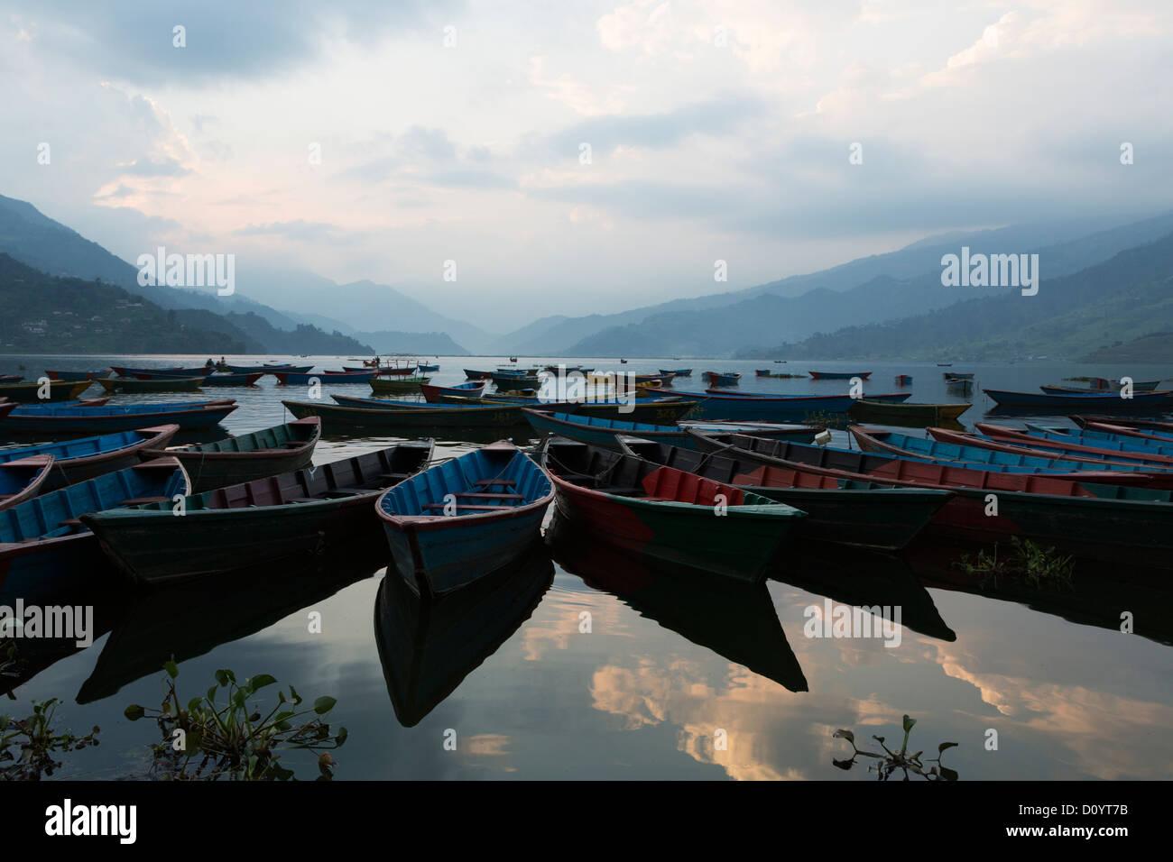 Wooden boats aligned on Phewa lake in Pokhara, Nepal - Stock Image