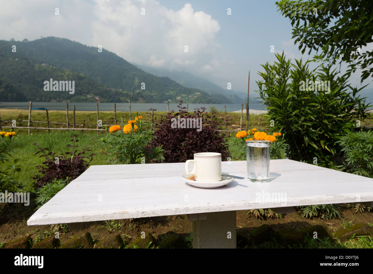 cup of coffe and a glass of water on a simple wooden table by the stunning Phewa lake in Pokhara in Nepal. - Stock Image
