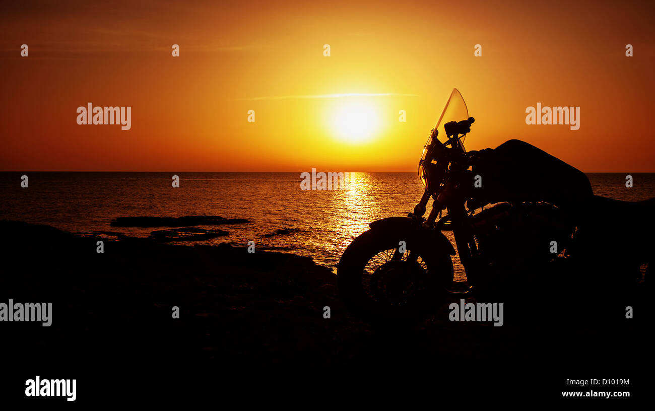 Picture of luxury motorcycle on the beach in night, silhouette of motorbike on sunset, Harley Davidson, active life - Stock Image