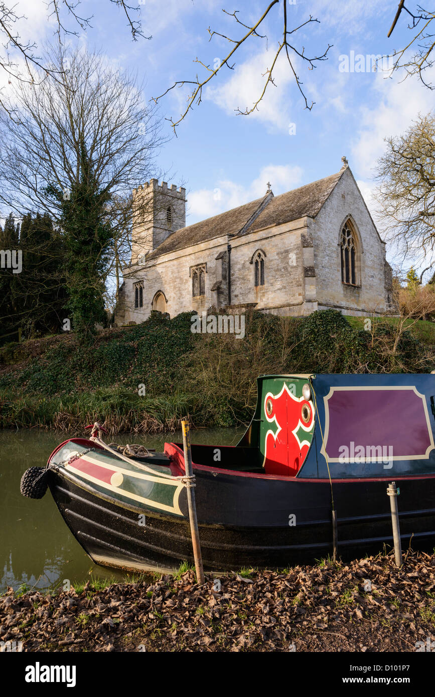 Narrowboat on the Oxford Canal by Holy Cross Church, Shipton-on-Cherwell Oxfordshire England UK - Stock Image