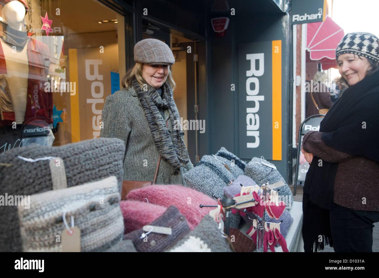 Woman at stall selling wool cushions Christmas street fair Woodbridge, Suffolk, England - Stock Image