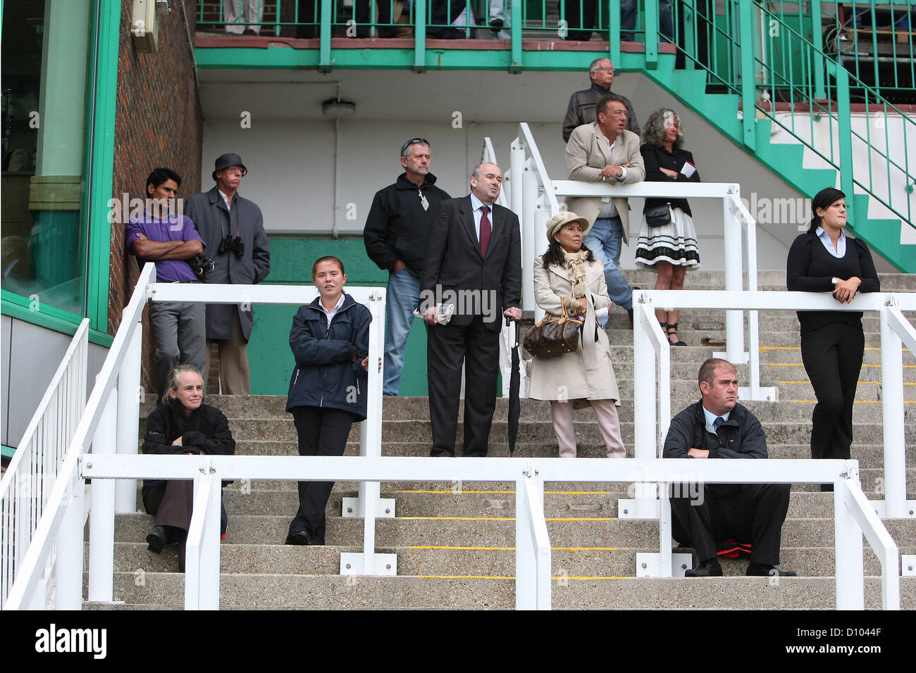 A typical poor crowd watch midweek racing in Britain - Stock Image