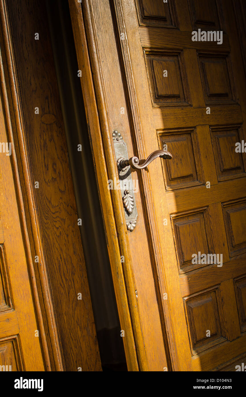 An old heavy wooden door opening a small gap Stock Photo