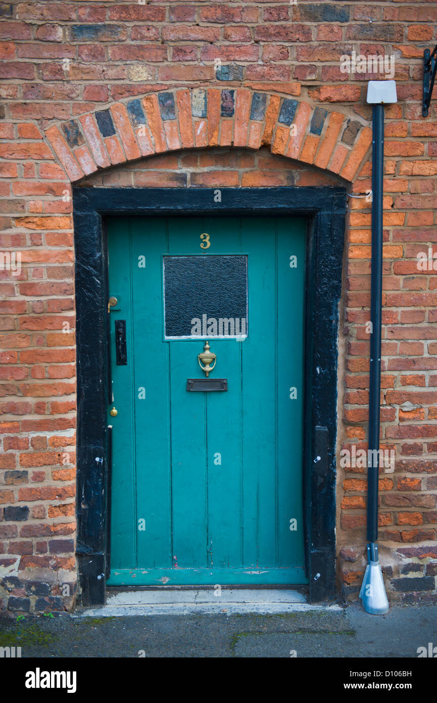 Turquoise Painted Front Door With Black Frame Of Cottage
