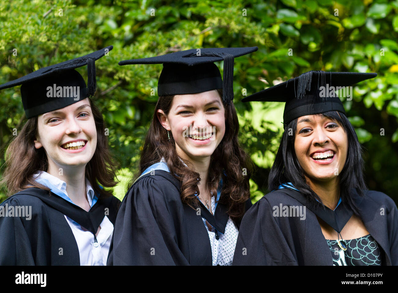 Three girls laugh whilst wearing a graduant mortar board and gown ...