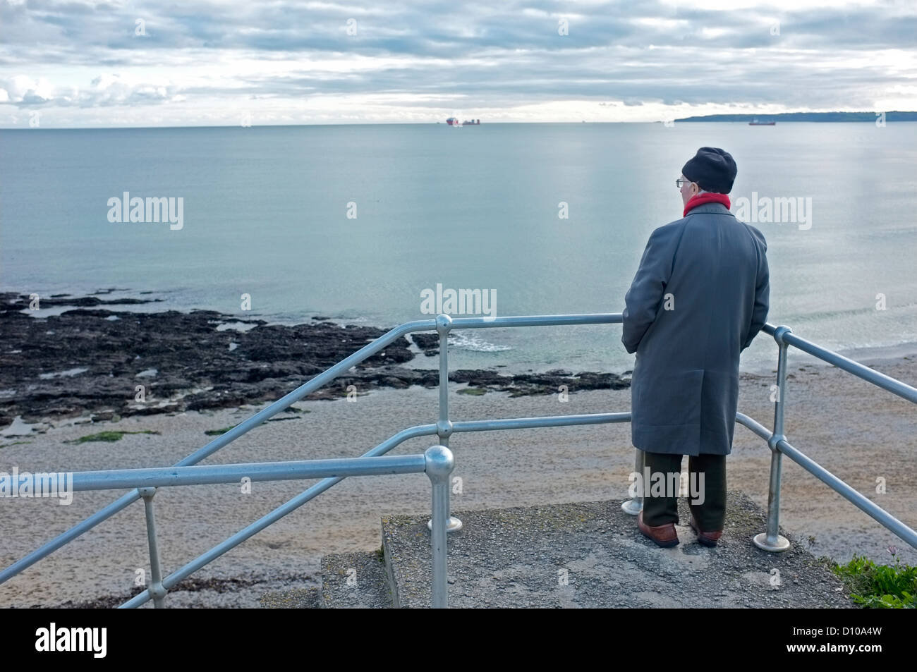 An old man looks out on a placid sea ay Gyllyngvase beach  in Cornwall, UK - Stock Image