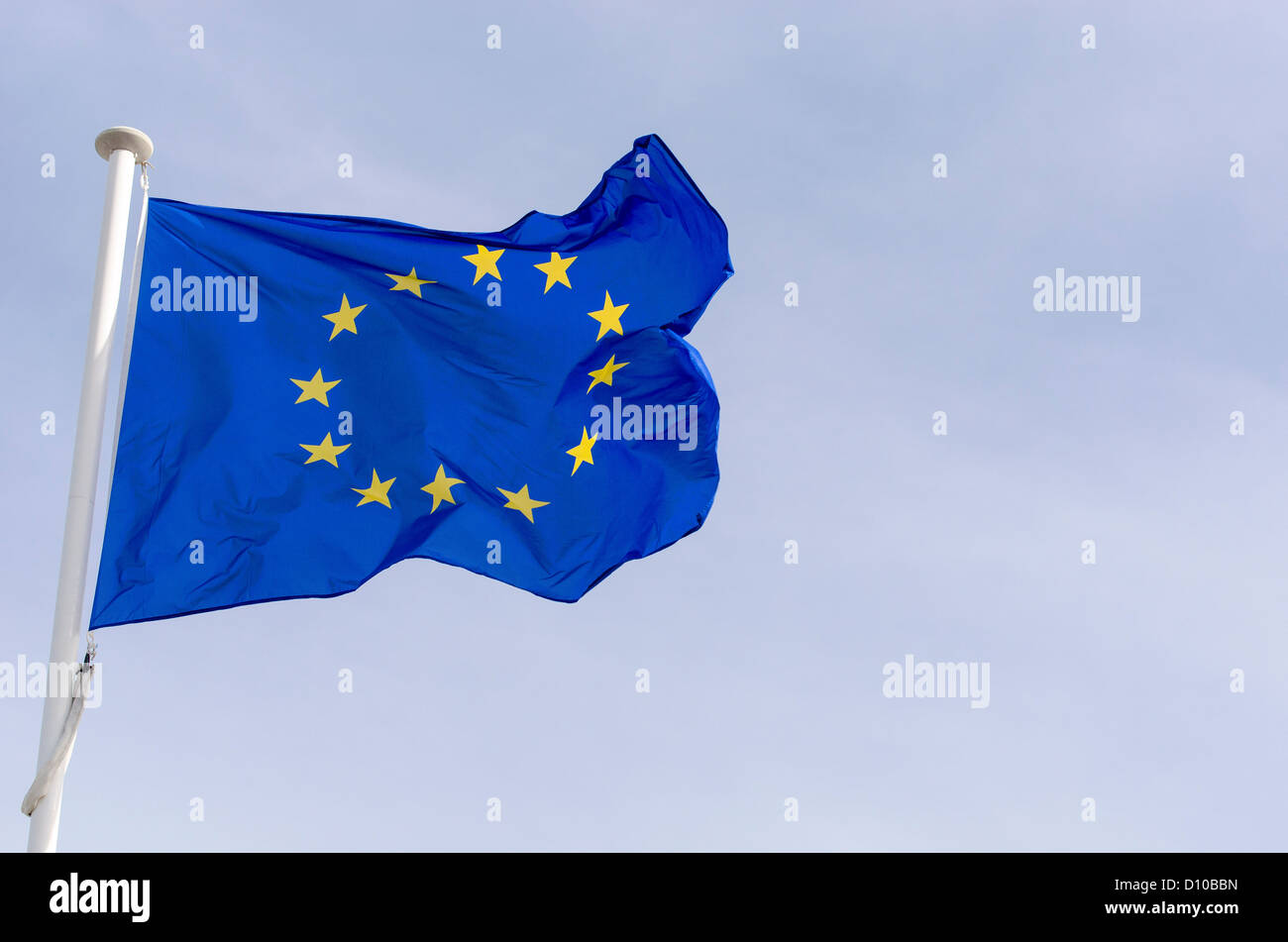 European Union flag flying in the wind in sky a slightly cloudy. - Stock Image