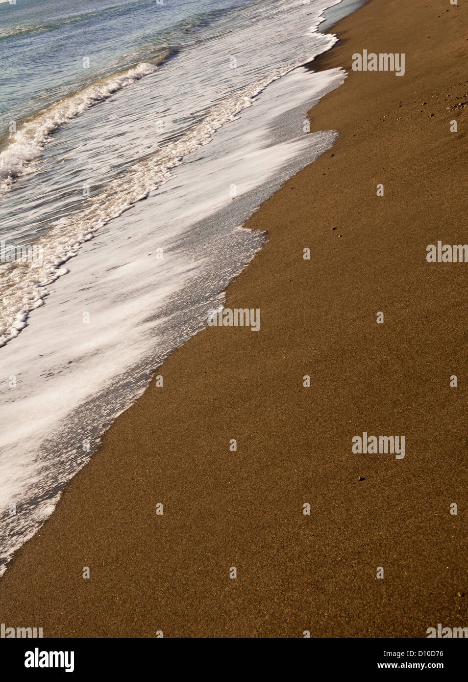 White waves breaking on a sandy beach - Stock Image