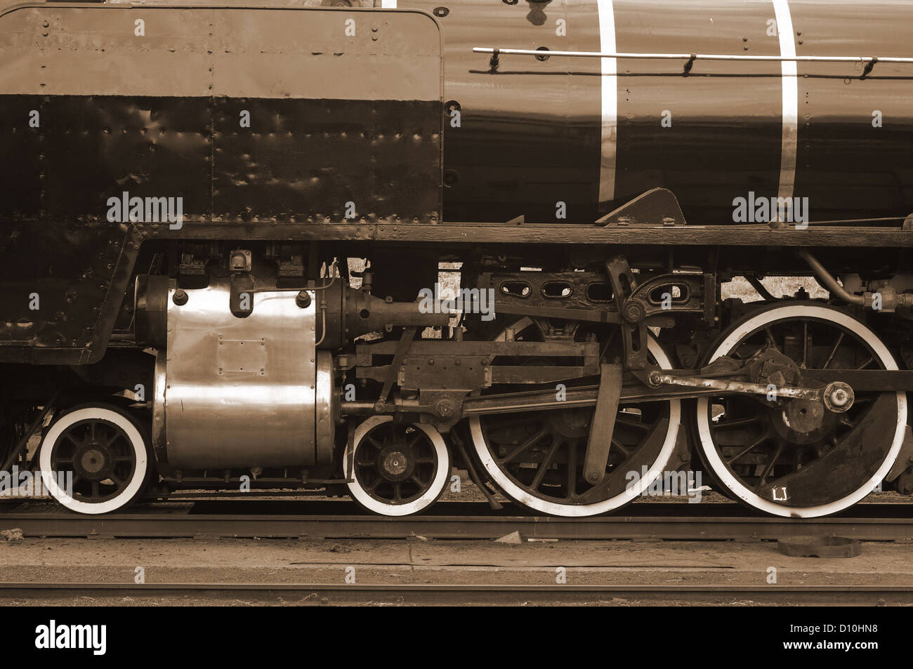 Steam train locomotive moving parts, gears and wheels in sepia - Stock Image