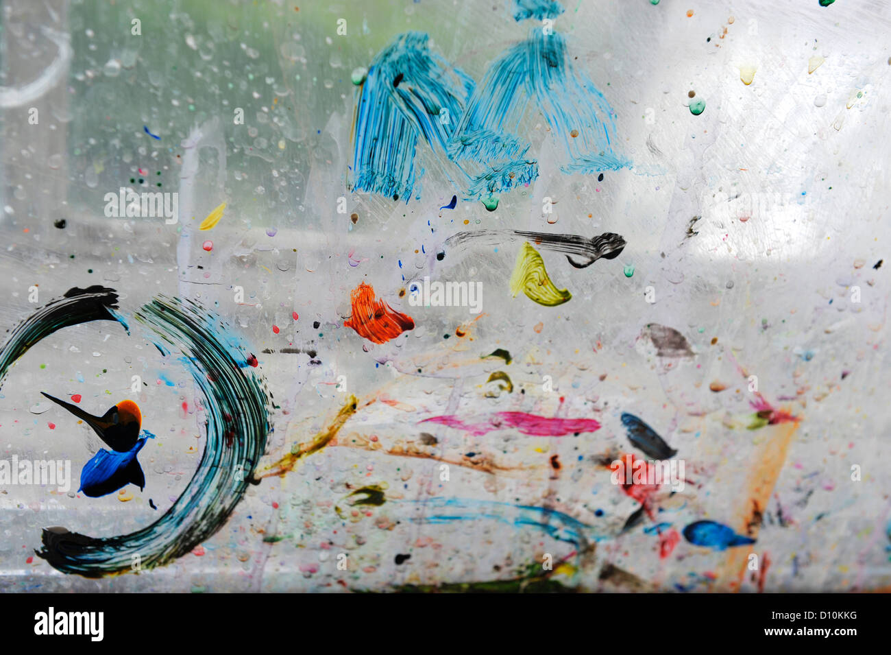Paint spatters and brush marks on the window pane of an artists' studio - Stock Image