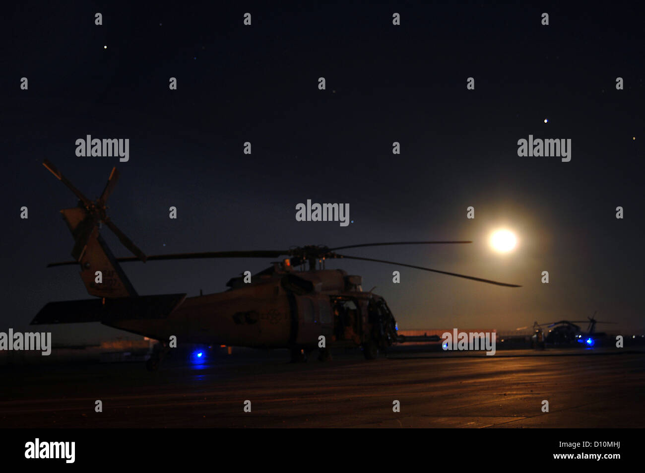 An HH-60G Pave Hawk from the 26th Expeditionary Rescue Squadron sits ready to respond to an alert call on the ramp - Stock Image