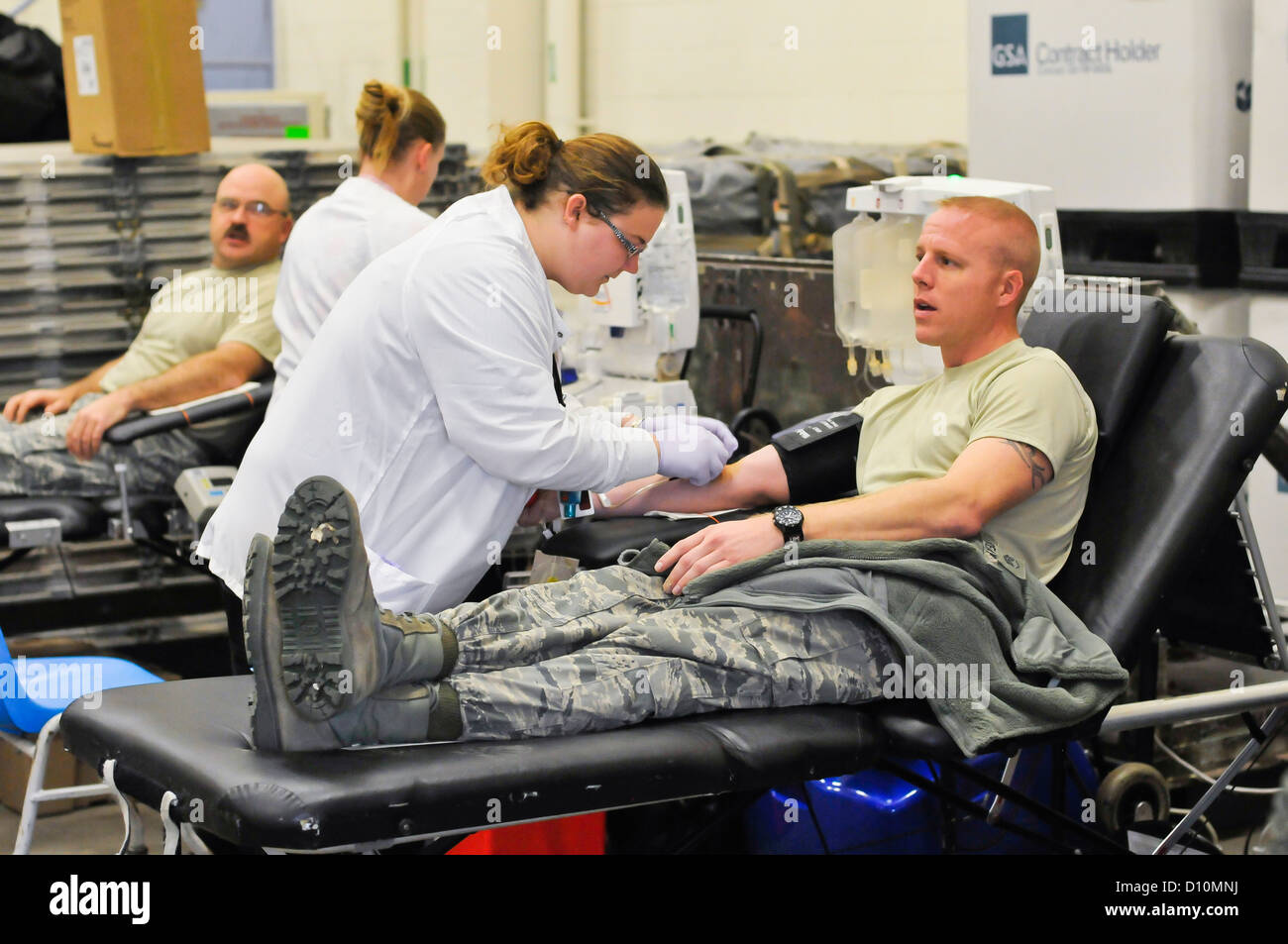 An Airmen from the 182nd Airlift Wing, Peoria, Ill. is about to be pricked with a needle during the blood drive. - Stock Image