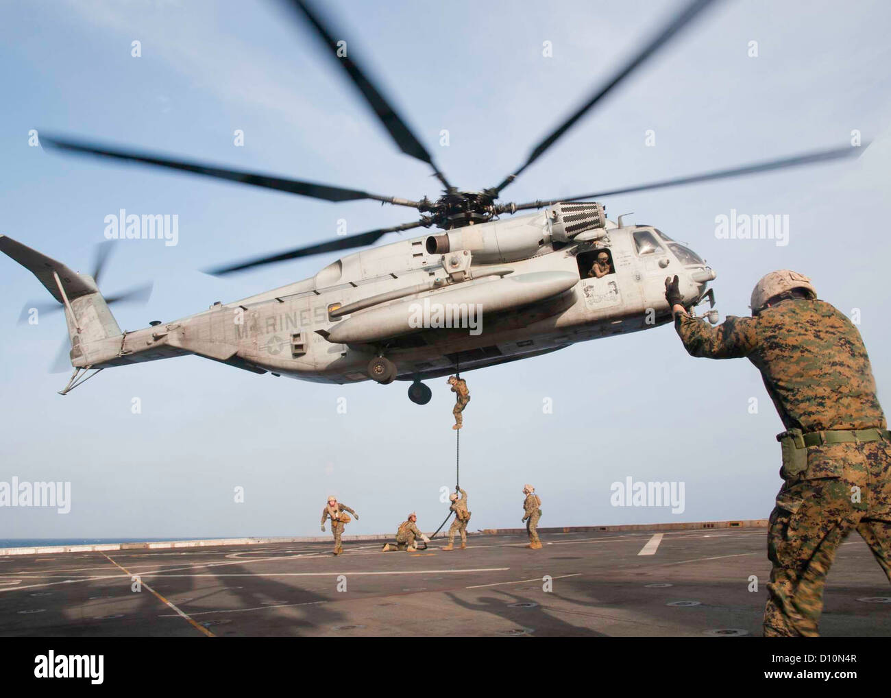 Marines assigned to the 24th Marine Expeditionary Unit (24th MEU) conduct fast-rope drills from a CH-53E Super Stallion - Stock Image