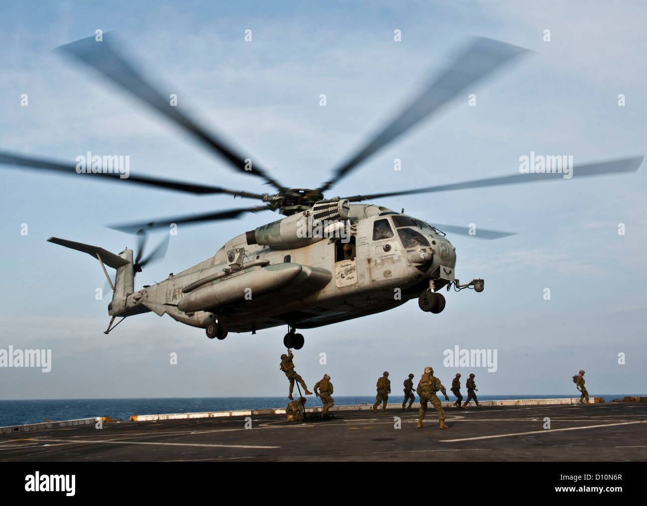 A CH-53E Super Stallion helicopter hovers above the flight deck of the amphibious transport dock ship USS New York - Stock Image